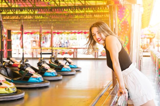 Glimlachende jonge vrouw die dichtbij van de rit van de bumperauto geniet