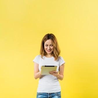 Glimlachende jonge vrouw die digitale tablet gebruiken tegen gele achtergrond