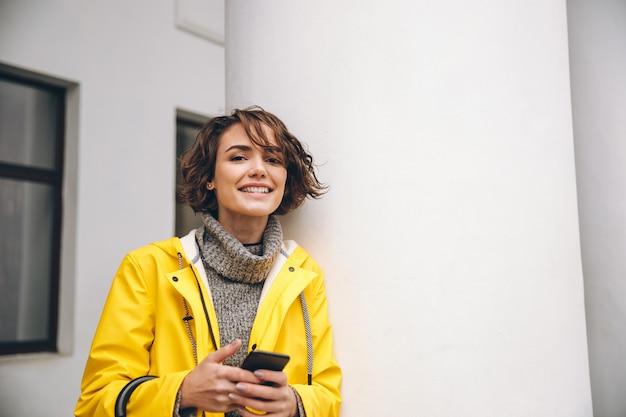 Glimlachende jonge vrouw die door mobiele telefoon babbelt. zoek camera.