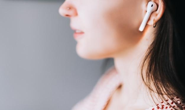Glimlachende jonge vrouw die draadloze oortelefoons met behulp van.