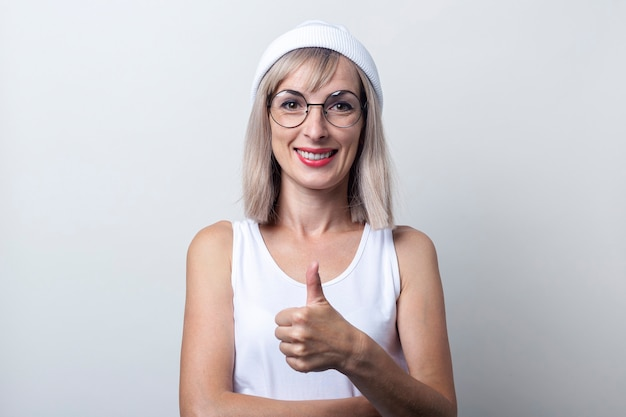 Glimlachende jonge vrouw die duim omhoog gebaarklasse op lichte achtergrond toont.