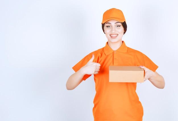 Glimlachende jonge vrouw die duim omhoog gebaart en pakket op witte muur houdt