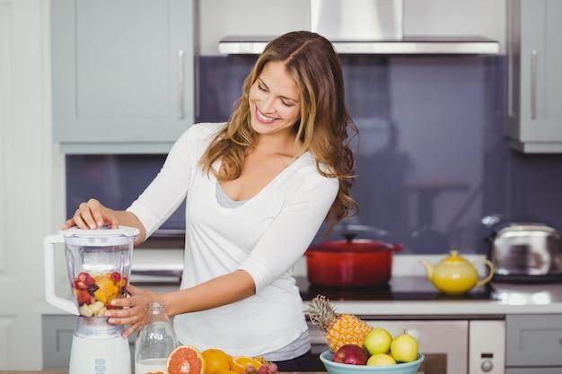 Glimlachende jonge vrouw die een juicer gebruikt