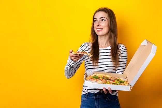 Glimlachende jonge vrouw die een plak van hete verse pizza met verpakking op geel eet.