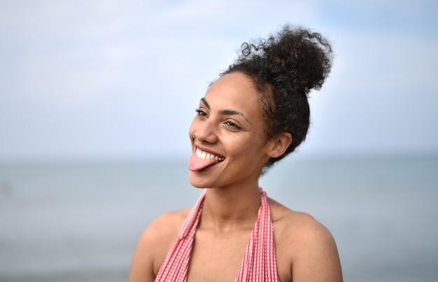 Glimlachende jonge vrouw die een zwempak op het strand draagt - het concept van geluk