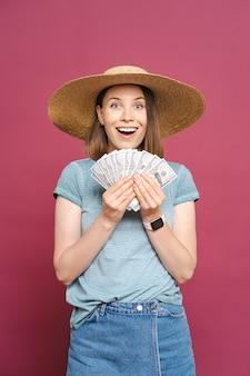 Glimlachende jonge vrouw die geld aanhoudt op roze muur