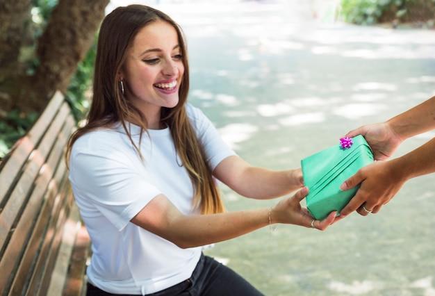 Glimlachende jonge vrouw die gift van haar vriend ontvangt