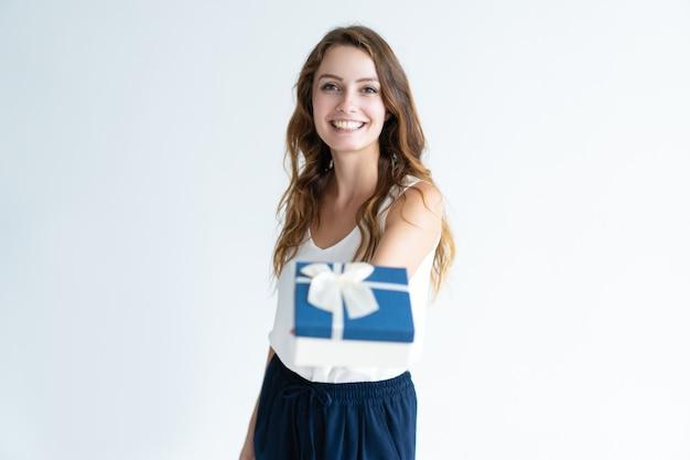 Glimlachende jonge vrouw die giftdoos met lint geeft
