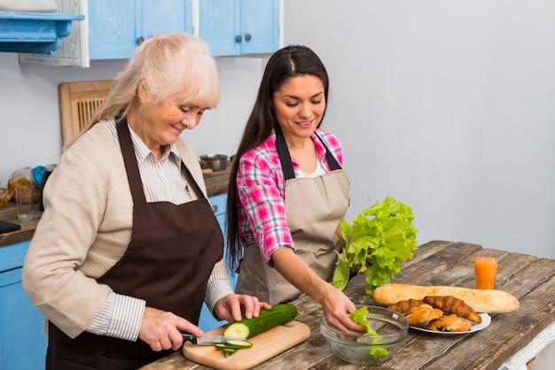 Glimlachende jonge vrouw die haar hogere moeder voor het voorbereiden van salade in de keuken helpen