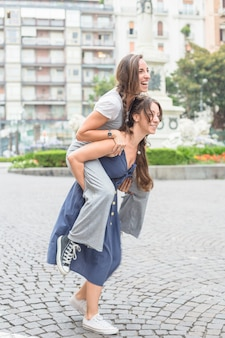 Glimlachende jonge vrouw die haar meisjestribbing op rit neemt op straat