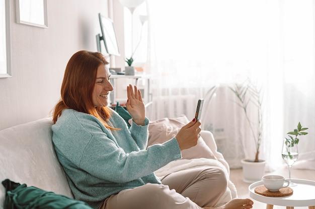 Glimlachende jonge vrouw die haar mobiele telefoon gebruikt terwijl ze thuis op de bank zit