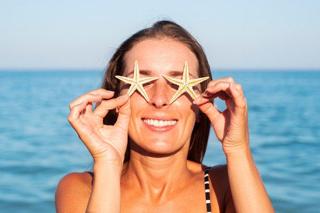Glimlachende jonge vrouw die haar ogen bedekt met zeester op de achtergrond van de zee.