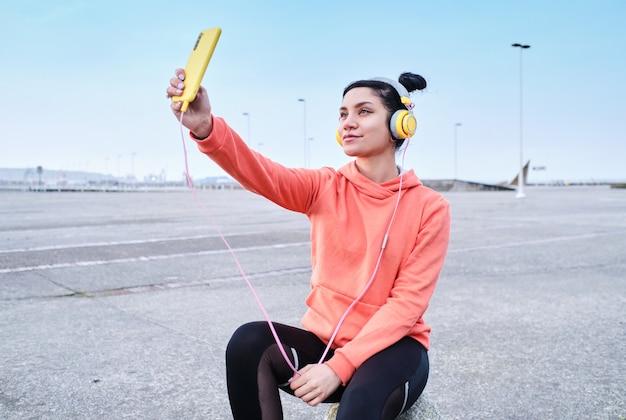 Glimlachende jonge vrouw die haar smarphone gebruikt om een videogesprek te voeren