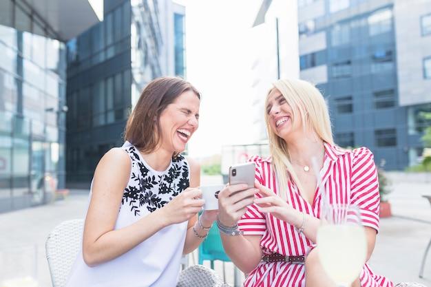 Glimlachende jonge vrouw die haar tonen mobiel aan de koffiekop van de vriendenholding