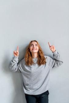 Glimlachende jonge vrouw die haar vingers richten die omhoog tegen grijze muur naar omhoog kijken
