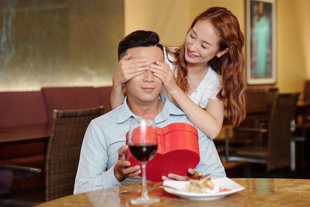 Glimlachende jonge vrouw die haar vriendje verrast, zijn ogen bedekt en een romantisch cadeau geeft