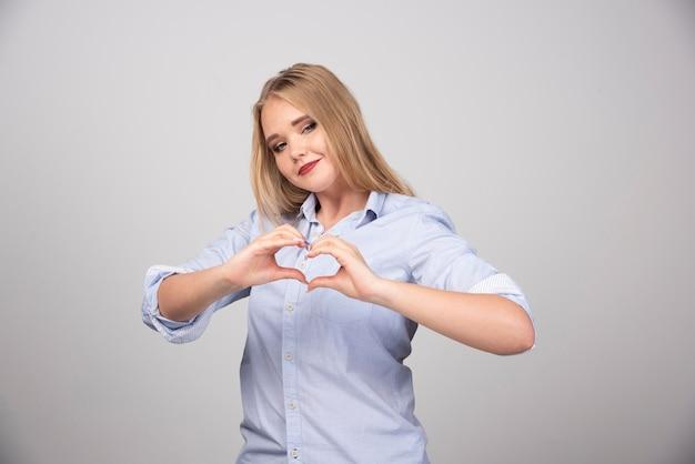 Glimlachende jonge vrouw die hart met twee handen toont tegen grijze muur.