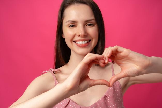 Glimlachende jonge vrouw die hartteken met handen gebaart die liefde tonen