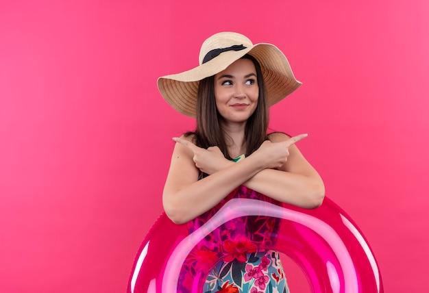Glimlachende jonge vrouw die hoed draagt die zwemt en met vingers aan kanten op geïsoleerde roze muur toont