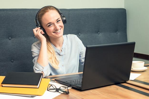 Glimlachende jonge vrouw die hoofdtelefoons draagt en voor open laptop bij een lijst op het kantoor zit.