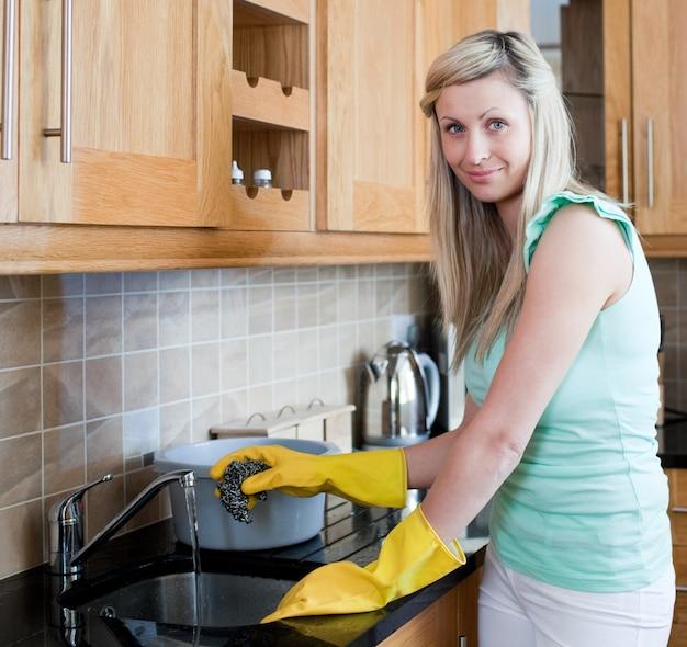 Glimlachende jonge vrouw die in een keuken schoonmaakt