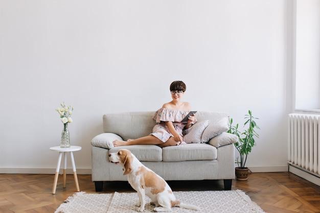 Glimlachende jonge vrouw die in glazen met glimlach kijken naar beagle hond zittend op een tapijt naast de bank