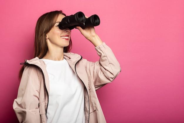Glimlachende jonge vrouw die in jas door een verrekijker kijkt