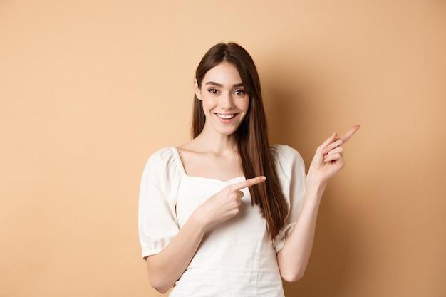 Glimlachende jonge vrouw die in kleding opzij wijst en tevreden kijkt, goede promoovereenkomst toont, die zich op beige achtergrond bevindt.