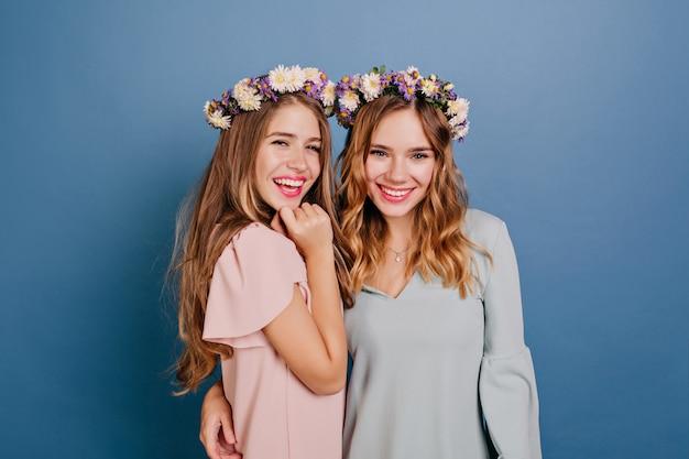 Glimlachende jonge vrouw die in kroon haar zus op blauwe muur omhelst