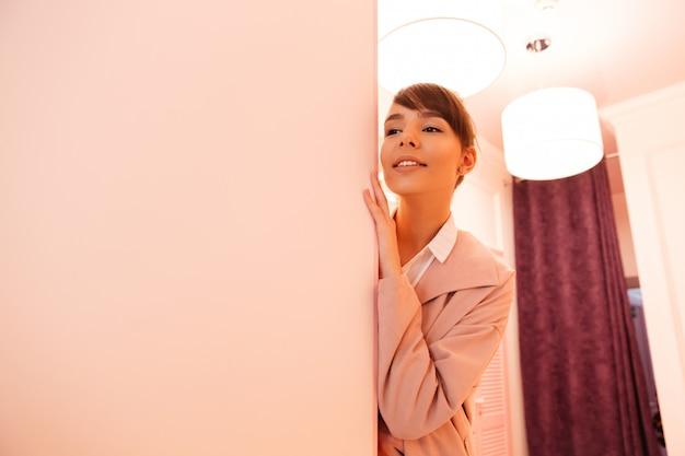 Glimlachende jonge vrouw die in laag op de muur leunt