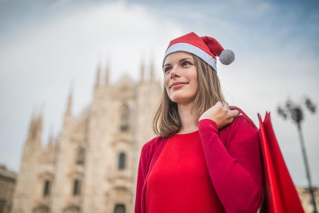 Glimlachende jonge vrouw die in milaan, italië winkelt
