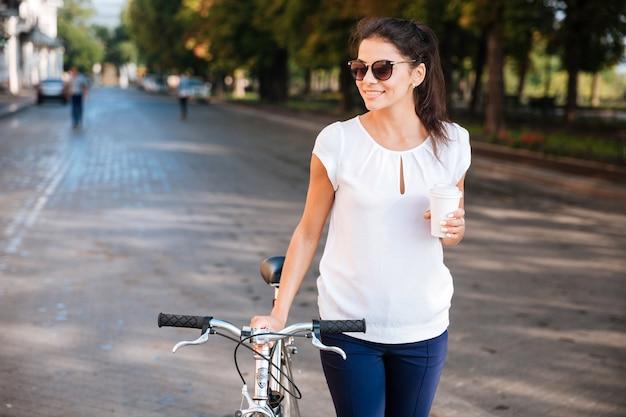 Glimlachende jonge vrouw die in zonnebril met fiets en afhaalkoffie loopt