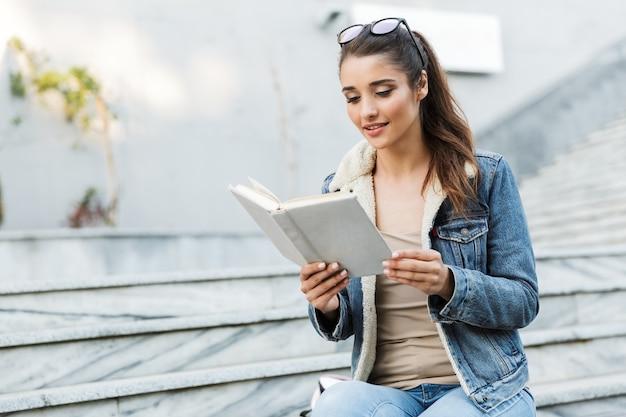 Glimlachende jonge vrouw die jasje zittend op een bankje buiten draagt, het lezen van boek