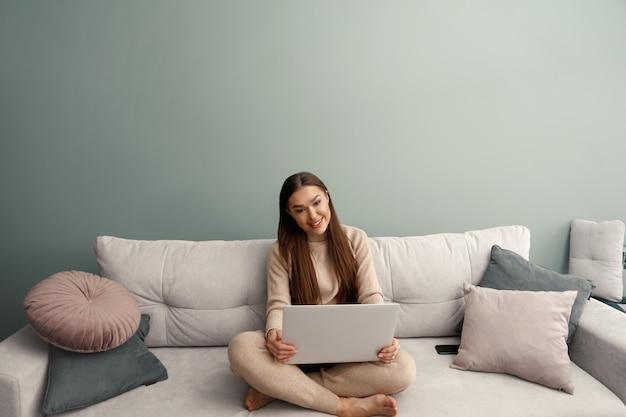 Glimlachende jonge vrouw die laptop gebruikt, thuis op de bank zit, mooi meisje winkelt of online chat in een sociaal netwerk, plezier heeft, film kijkt, freelancer werkt.