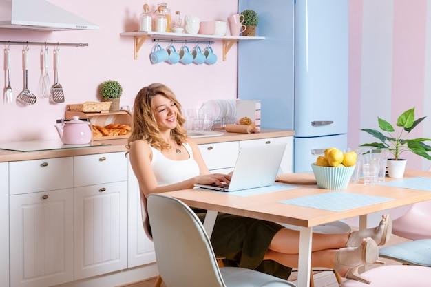 Glimlachende jonge vrouw die laptop in de keuken thuis met behulp van. blonde vrouw werkt op computer, freelancer of blogger thuis werken