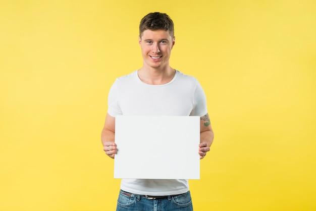 Glimlachende jonge vrouw die leeg aanplakbiljet toont tegen gele achtergrond