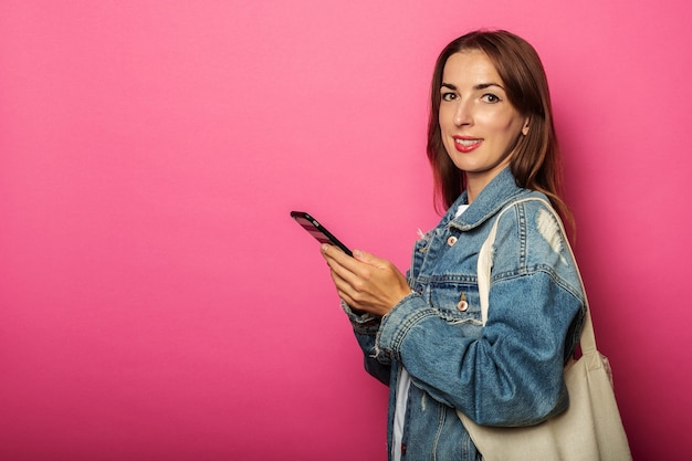 Glimlachende jonge vrouw die met ecozak telefoon bekijkt