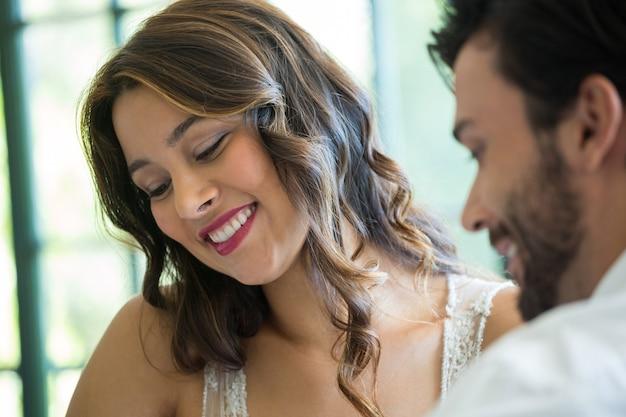 Glimlachende jonge vrouw die met man in restaurant daten