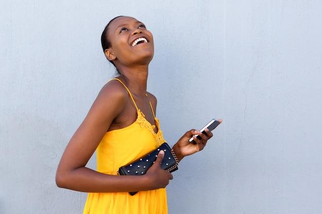 Glimlachende jonge vrouw die met mobiele telefoon loopt