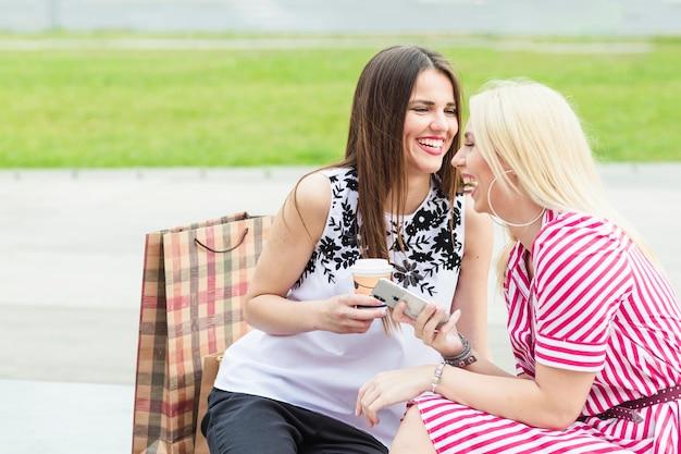 Glimlachende jonge vrouw die mobiele telefoonzitting met vriend houdt die meeneemkoffiekop houdt