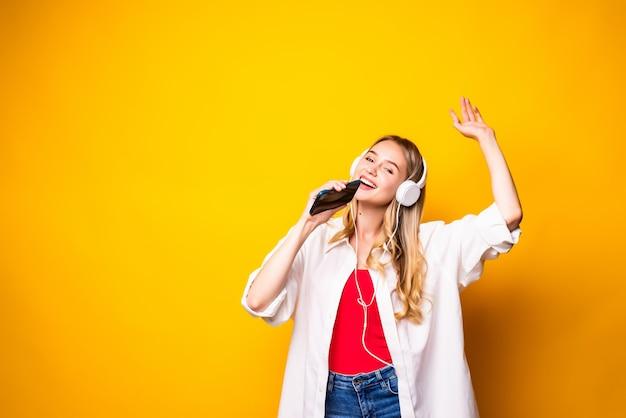 Glimlachende jonge vrouw die muziek in hoofdtelefoons luistert en smartphone gebruikt die over gele muur wordt geïsoleerd
