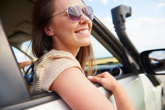 Glimlachende jonge vrouw die naar het uitzicht kijkt tijdens een roadtrip