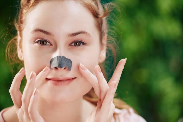 Glimlachende jonge vrouw die neusstrook toepast om poriën op haar neus schoon te maken