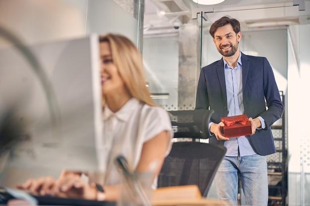 Glimlachende jonge vrouw die op de computer werkt terwijl een mannelijke collega achter haar staat en een geschenkdoos vasthoudt