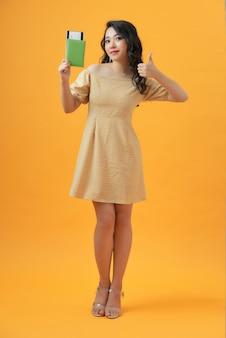Glimlachende jonge vrouw die op geel wordt geïsoleerd