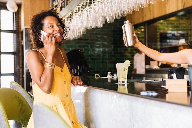 Glimlachende jonge vrouw die op mobiele telefoon bij barteller spreekt