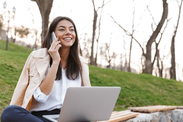 Glimlachende jonge vrouw die op mobiele telefoon spreekt