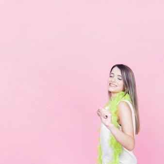 Glimlachende jonge vrouw die op roze achtergrond danst