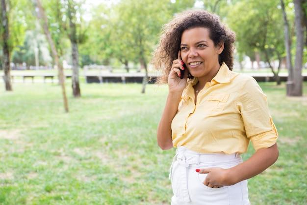 Glimlachende jonge vrouw die op telefoon in stadspark spreekt
