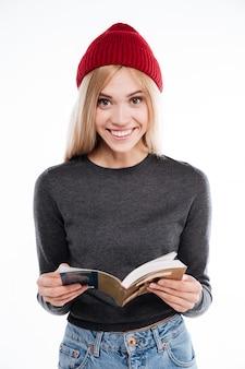 Glimlachende jonge vrouw die open boek houdt en camera bekijkt